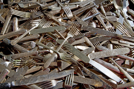 mishmash: A haphazard display of antique silverware, including forks, knives and spoons.