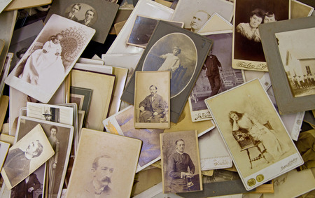 CHARLOTTE, NC - FEBRUARY 7, 2015:  A jumble of old, fading photographs showing people of various ages on sale at the Metrolina Expo Antique Show.