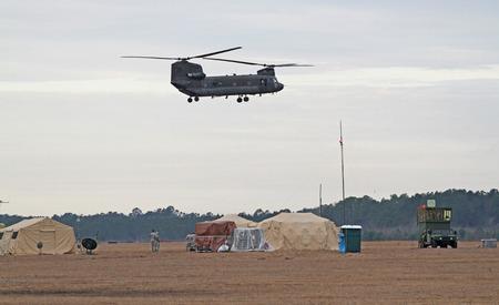 chinook: GEORGETOWN, SC - 8 Marzo 2015: Un elicottero dell'esercito americano National Guard Chinook passa sopra un impianto di controllo del traffico aereo portatile durante l'Operazione Vigilant Guardia, un trapano disastro simulando un uragano di categoria 4 fare landfall sul South Carolin
