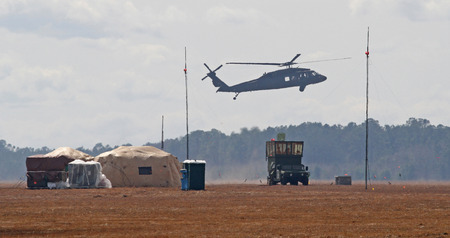 blackhawk helicopter: GEORGETOWN, SC - March 9, 2015:  A U.S. Army National Guard Blackhawk helicopter hovers over a portable air traffic control installation during Operation Vigilant Guard, a disaster drill simulating a Category 4 hurricane making landfall on the South Carol Editorial