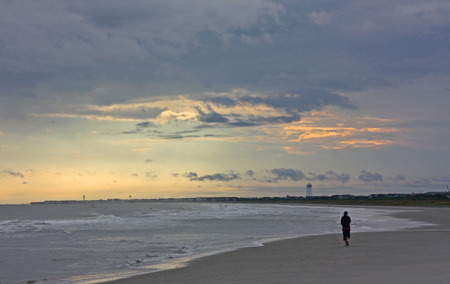 unsettled: A solitary beach walker in unsettled weather