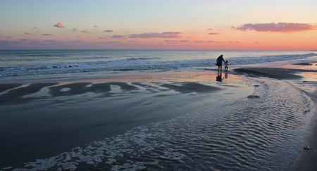 An adult and child walk on a beach at sunset