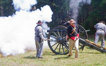 armaments: HUNTERSVILLE NC  JUNE 6 2015:  Reenactors in Confederate army uniforms fire a 10pound parrott gun during an American Civil War battle reenactment at Historic Latta Plantation. Editorial