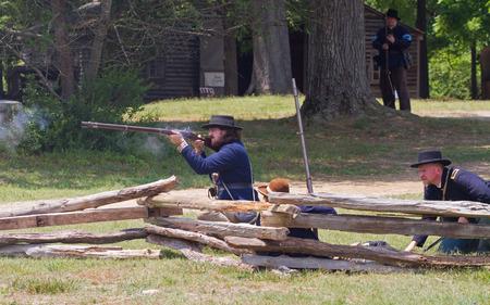 recreate: HUNTERSVILLE NC  JUNE 6 2015:  Reenactors in Union Army uniforms recreate an American Civil War battle at Historic Latta Plantation.