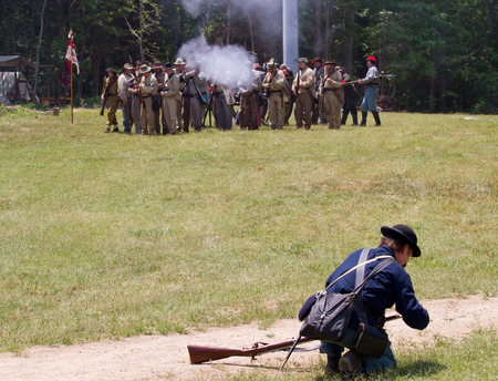 recreate: HUNTERSVILLE NC  JUNE 6 2015:  Reenactors in Confederate and Union army uniforms recreate an American Civil War battle at Historic Latta Plantation. Editorial
