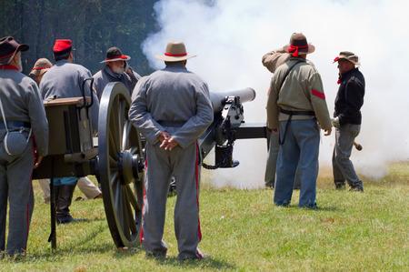 yankees: HUNTERSVILLE NC  JUNE 6 2015:  Reenactors in Confederate army uniforms fire a 10pound parrott gun during an American Civil War battle reenactment at Historic Latta Plantation. Editorial