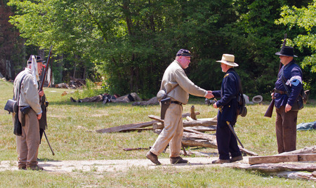 armaments: HUNTERSVILLE NC  JUNE 6 2015:  Reenactors in Confederate and Union army uniforms recreate a surrender ceremony during an American Civil War battle reenactment at Historic Latta Plantation.