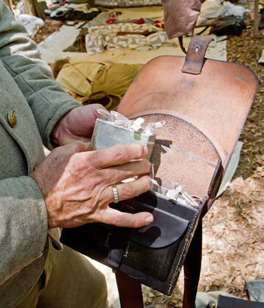armaments: HUNTERSVILLE NC  JUNE 6 2015:  Closeup of a Confederate ammunition pouch worn by a participant in an American Civil War battle reenactment at Historic Latta Plantation.