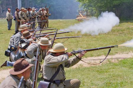 recreate: HUNTERSVILLE NC  JUNE 6 2015:  Reenactors in Confederate uniforms recreate an American Civil War battle at Historic Latta Plantation. Editorial