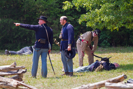 recreate: HUNTERSVILLE, NC - JUNE 6 2015:  Reenactors in Confederate and Union army uniforms recreate an American Civil War battle at Historic Latta Plantation. Editorial