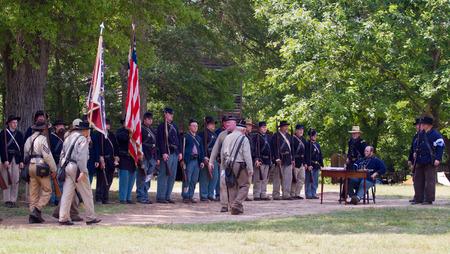 recreate: HUNTERSVILLE, NC - JUNE 6 2015:  Reenactors in Confederate and Union army uniforms recreate a surrender ceremony during an American Civil War battle reenactment at Historic Latta Plantation.