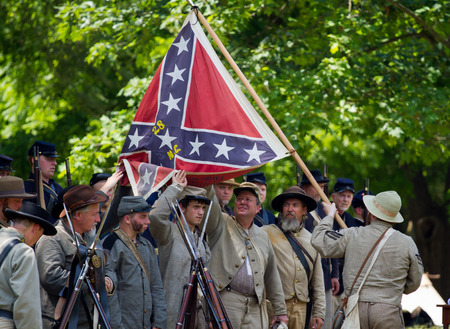 armaments: HUNTERSVILLE, NC - JUNE 6 2015:  Reenactors in Confederate and Union army uniforms recreate a surrender ceremony during an American Civil War battle reenactment at Historic Latta Plantation.