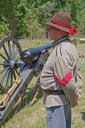 armaments: HUNTERSVILLE, NC - JUNE 6 2015:  - A reenactor in a Confederate army uniform stands next to a 10pound Parrott gun during an American Civil War battle reenactment at Historic Latta Plantation. Editorial