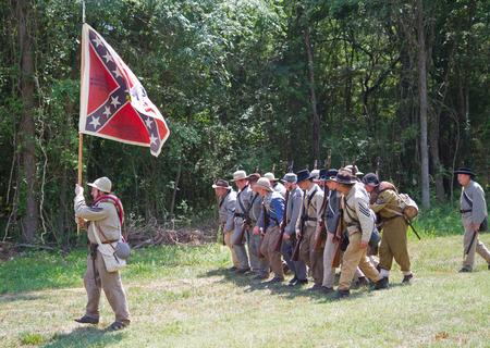 armaments: HUNTERSVILLE, NC - JUNE 6 2015:  Reenactors in Confederate uniforms march under their battle flag during an American Civil War reenactment at Historic Latta Plantation. Editorial