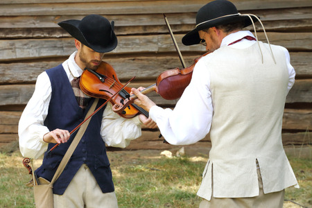 revolutionary war: MCCONNELLS, SC - July 11, 2015:  Violinists in colonial costumes perform during the American Revolutionary War recreation of the Battle of Hucks Defeat at Historic Brattonsville.  The Patriot victory was originally fought nearby on July 12, 1780.
