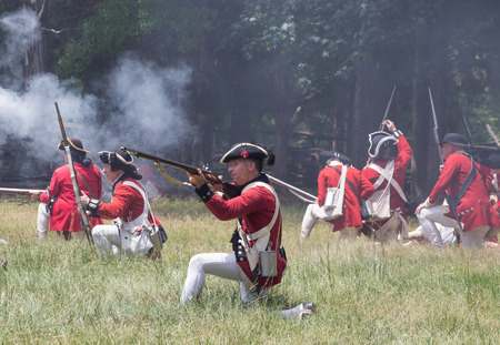 recreate: MCCONNELLS, SC - July 11, 2015:  American Revolutionary War reenactors in British uniforms recreate the Battle of Hucks Defeat at Historic Brattonsville.  The Patriot victory was originally fought nearby on July 12, 1780.