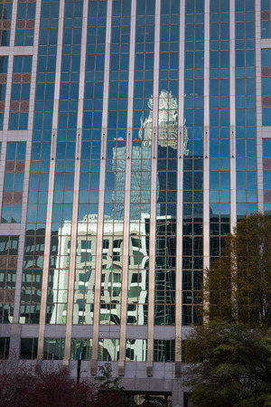 neighboring: CHARLOTTE, NC - December 12, 2015: A modern office tower in Charlotte, North Carolina, reflects images of its neighboring buildings on a sunny day.