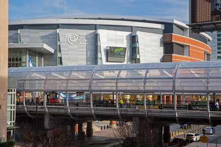 uptown: CHARLOTTE, NC - December 12, 2015: Time Warner Cable Arena in downtown Charlotte, North Carolina, home of the NBA Charlotte Hornets, with a Lynx light rail station in the foreground.