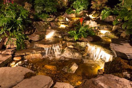 CHARLOTTE, Carolina del Norte - el 28 de de febrero de, 2016: Una muestra de la arquitectura del paisaje con la iluminación dramática noche en el Southern Spring Home Garden Show. Foto de archivo - 53204893