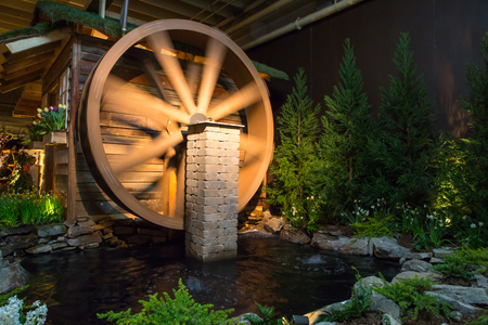 Rustic landscape design featuring a water wheel and pond. Stock Photo