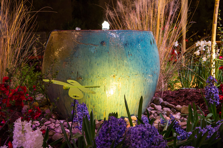 Dramatically lit pottery fountain in a garden setting.