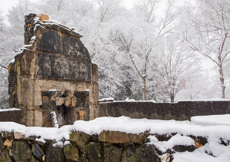 Stonework and fireplace of a ruined farm house in a snowstorm. Stock Photo
