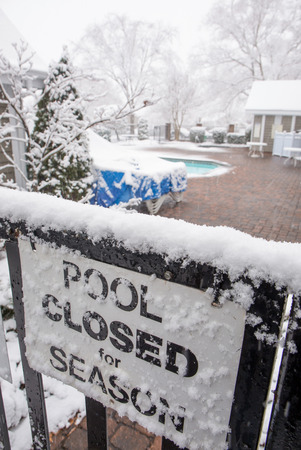 Closeup of a swimming pool closed sign in a snowstorm.