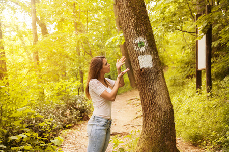 Confused young woman looking at a sign on a tree in the forest