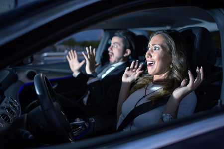 Business couple in car almost having an accident with headlight shining