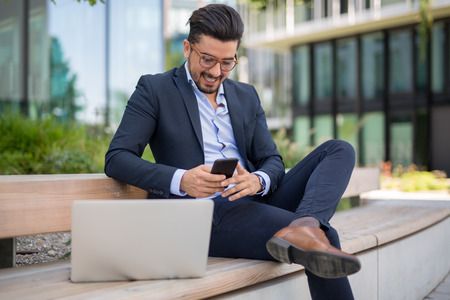 Handsome young businessman with laptop texting sms on his smartphone while smiling