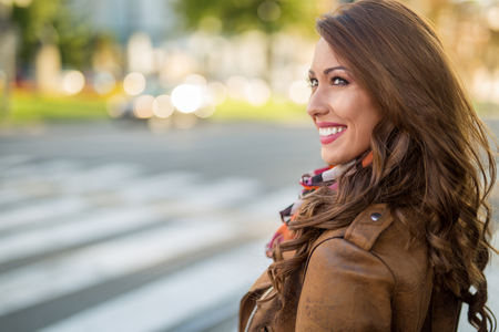 Beautiful young woman smiling while waiting at a cross walk at daytime