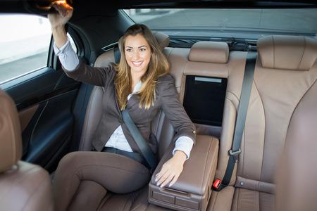 Beautiful business woman in a limousine smiling Reklamní fotografie
