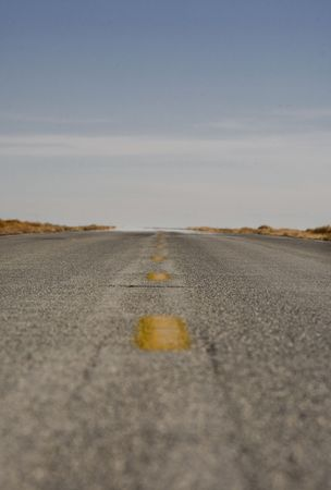 remoteness: A paved street heading off into the distance. Stock Photo