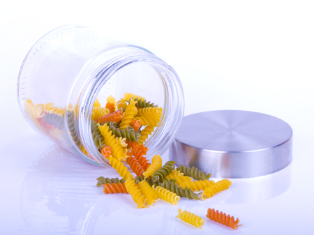 Close up of colorful rotini pasta in a glass jar isolated on white background