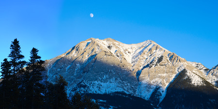 Mountain at sunset with moon in background