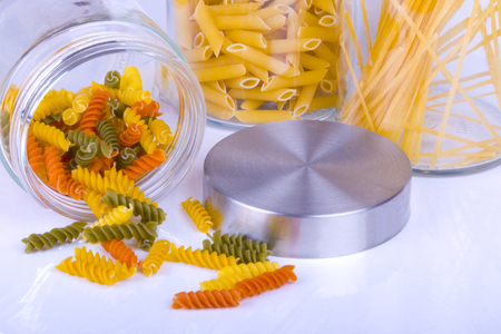 Close up of colorful rotini, penne, and spaghetti pasta in a glass jar isolated on white background