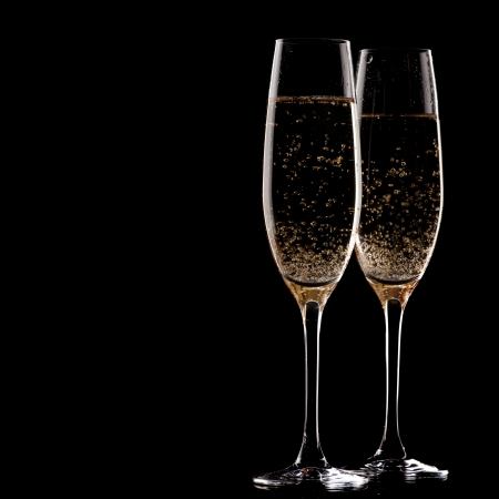 champagne flute: two glasses of champagne over black background
