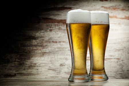 beer barrel: two glasses of beer over vintage wood background
