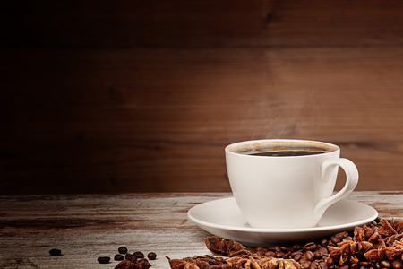 white cup of coffee over wooden background photo