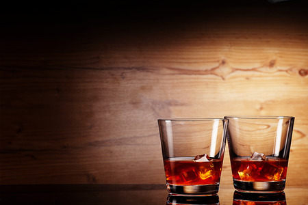 bar top: tho glasses of whiskey over woodenbackground Stock Photo