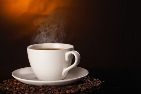 breakfast cup: cup of coffee and coffee beans over dark background