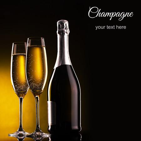 brindisi spumante: bottiglia di champagne e bicchieri su sfondo scuro