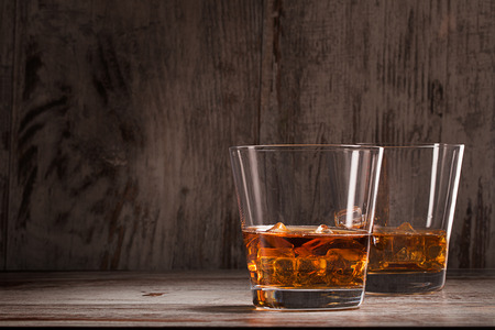 shooter drink: two glasses of whiskey over wooden background