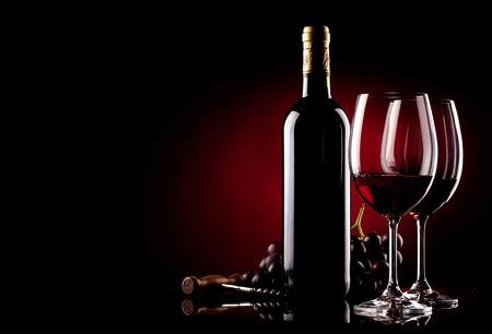 twee glazen wijn, fles, druiven en kurkentrekker Stockfoto