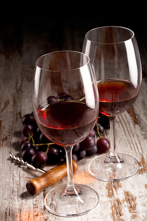 two glasses of wine, bottle, grapes and corkscrew