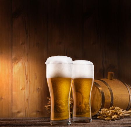 beer barrel: two glasses of beer, barrel and rye on wooden table. wooden background