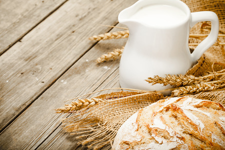 jug of milk, white bread, rye and sacking on wooden table photo