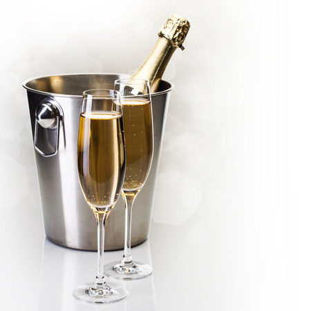 Champagne bottle in bucket with glasses of champagne in front of bokeh background photo