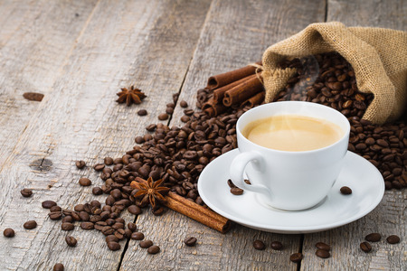 coffee cup on old wooden table and bag of coffee beans photo
