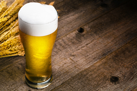 glass of beer and wheat on wooden table Standard-Bild